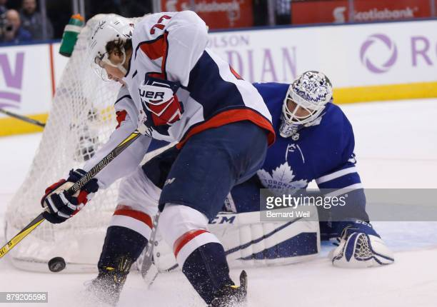 TORONTO ON NOVEMBER 25 Toronto Maple Leafs goalie Curtis McElhinney keeps an eye on the puck as Washington Capitals right wing TJ Oshie gets to it in...