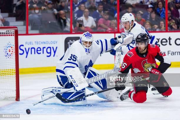 Toronto Maple Leafs goalie Curtis McElhinney scrambles cross the crease tracking a rebound off Ottawa Senators center Colin White during second...