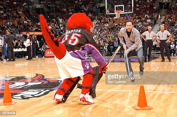 Toronto Maple Leafs goalie Ed Belfour takes a shot on the Toronto Raptor Mascot during a NBA Preseason game between the Toronto Raptors and the...