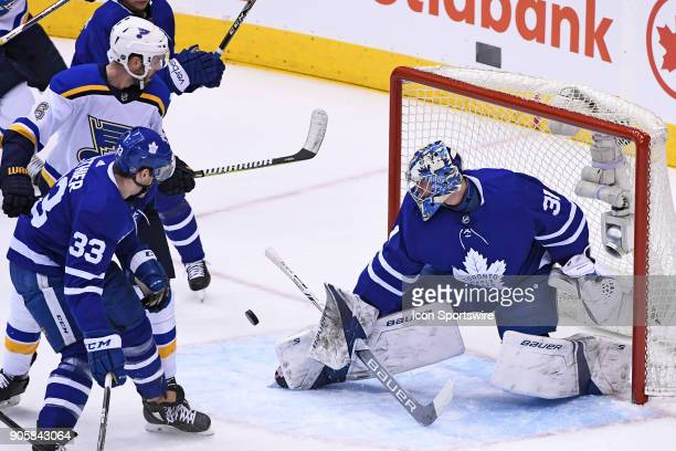 Toronto Maple Leafs Goalie Frederik Andersen makes a save in front of Center Frederik Gauthier and St Louis Blues Defenceman Joel Edmundson during...