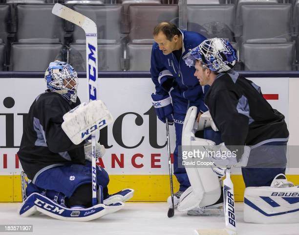 TORONTO ON OCTOBER 7 Toronto Maple Leafs goalie Jonathan Bernier Goaltending coach Piero Greco and goalie James Reimer talks near the side boards...
