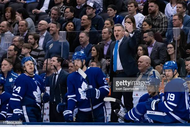 Toronto Maple Leafs Head Coach Sheldon Keefe waves to a player to come off the ice during the third period of the NHL regular season game between the...