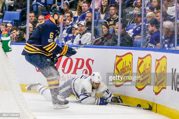 Toronto Maple Leafs Left Wing Matt Martin falls to the ice trying to control puck as Buffalo Sabres Defenseman Cody Franson closes in during the...