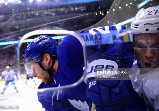 Toronto Maple Leafs right wing Connor Brown battles with Vancouver Canucks defenseman Ben Hutton during the first period in a game between the...