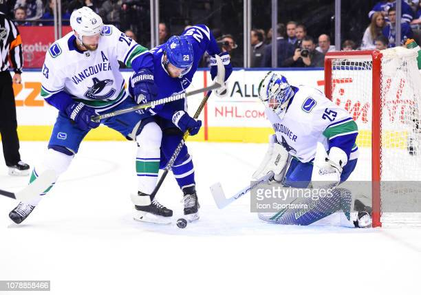 Toronto Maple Leafs right wing William Nylander battles for a puck with Vancouver Canucks defenseman Alexander Edler in front of Vancouver Canucks...