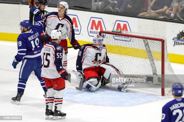 Toronto Marlies center Chris Mueller and Cleveland Monsters goalie Matiss Kivlenieks react after Mueller put the puck past Kivlenieks for the game...