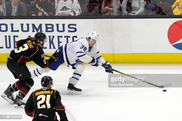 Toronto Marlies center Hudson Elynuik reaches for the puck during the third period of the American Hockey League game between the Toronto Marlies and...