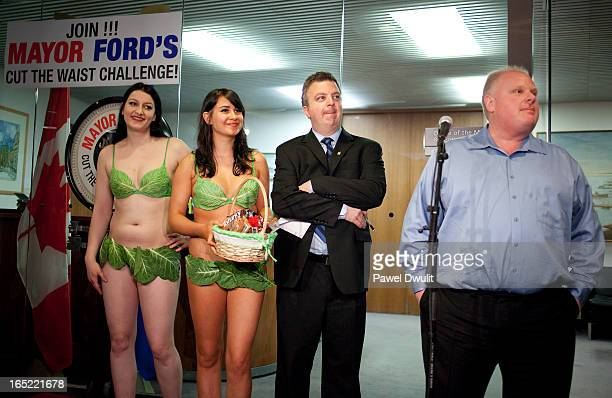 Toronto Mayor Rob Ford takes questions from the media following his weekly weigh in as PETA representatives Katy Ring and Emily Lavender watch at...