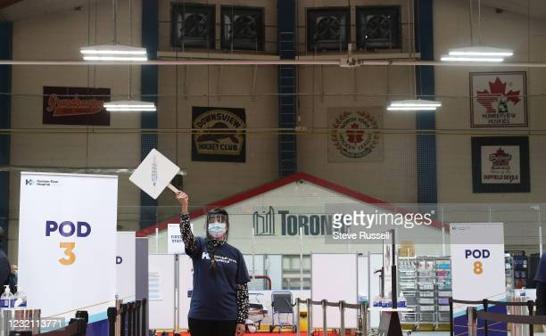 Toronto, ON- April 4 - Staff holding vaccine signs wave patients to their pods to be given the vaccine. The arena moves patients into one of eight...