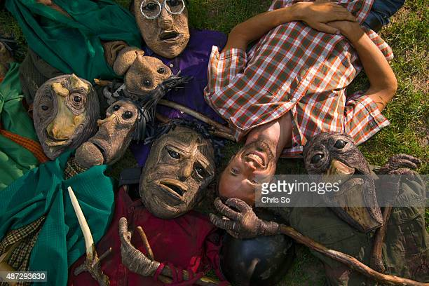 Toronto ON AUGUST 7 Puppet designer Zach Fraser lies amongst his hand made creations of character for Macbeth The puppets are made of string yarn...