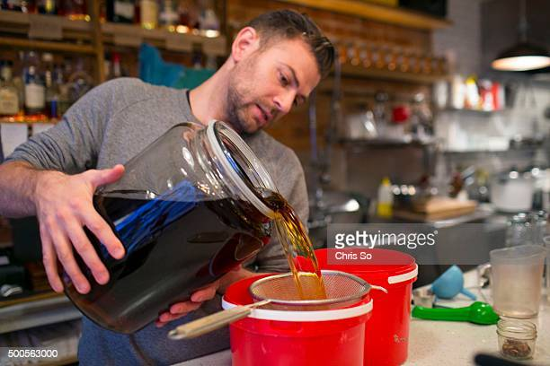 Toronto ON NOVEMBER 27 2015 Rhum Corner bar manager David Greig strains out spices that have flavored a batch of ginger beer Corey Mintz checks in at...