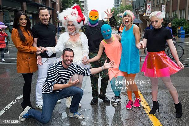 Toronto Ontario JUNE Pride Executive Director Mathieu Chantelois kneeling poses with parade marshals from left Celina Jaitly David Furnish Cyndi...