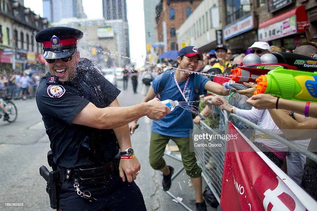 Toronto Police officer has water fight with party goers in the annual Pride Parade in Toronto on July 3, 2011