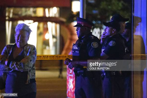 TOPSHOT Toronto Police officers stand watch at Danforth St at the scene of a shooting in Toronto Ontario Canada on July 23 2018 A gunman opened fire...