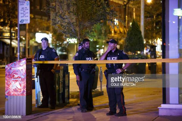 Toronto Police officers stand watch at Danforth St at the scene of a shooting in Toronto Ontario Canada on July 23 2018 A gunman opened fire in...