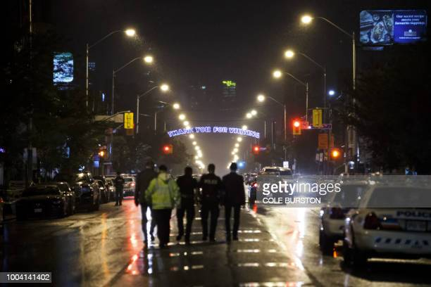 TOPSHOT Toronto Police officers work on Danforth St at the scene of a shooting in Toronto Ontario Canada on July 23 2018 A gunman opened fire in...