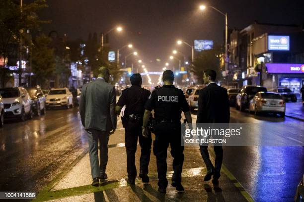 Toronto Police officers work on Danforth St at the scene of a shooting in Toronto Ontario Canada on July 23 2018 A gunman opened fire in central...