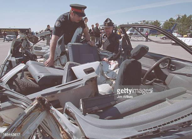 STREET 1 / 05/22/02 Toronto police Sergeant Brian Kenny LEFT and OPP Senior Constable Steve Barcham examine the remains of a car wrecked in a street...