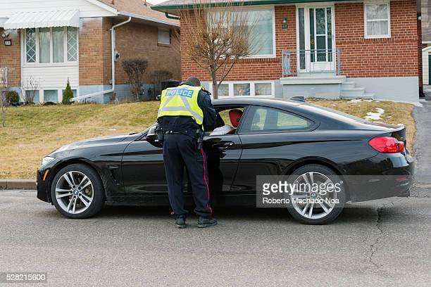 Toronto Police Service officer giving a speeding ticket to a driver parked on the side of the road