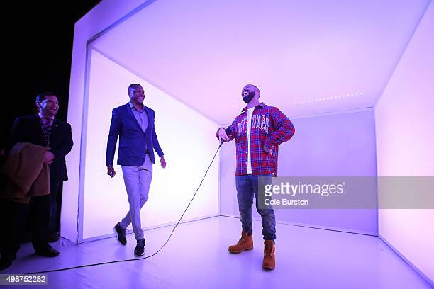 Toronto Rapper Drake busts a move with Toronto Raptors General Manager Masai Ujiri in a 'Hotline Bling' installation at the Air Canada Centre in...