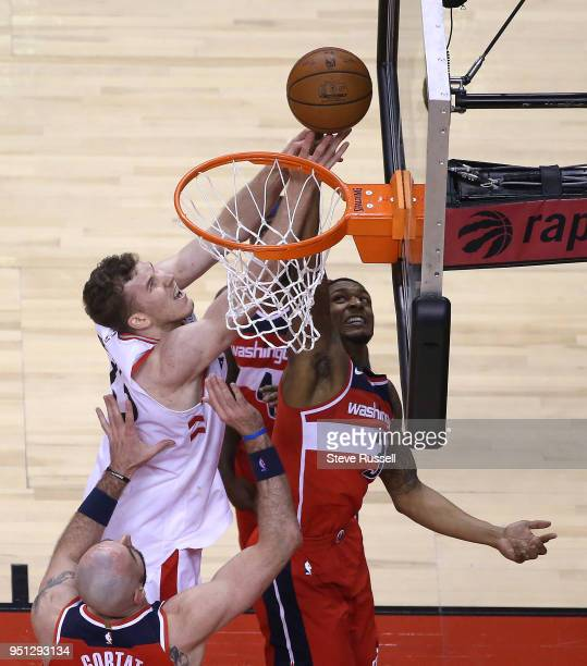 Toronto Raptors center Jakob Poeltl and Washington Wizards guard Bradley Beal reach for a rebound as the Toronto Raptors play game five of their...