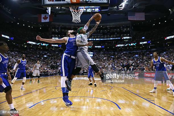 Toronto Raptors center Jonas Valanciunas blocks Boston Celtics guard Isaiah Thomas late in the game as the Toronto Raptors wearing their throw back...