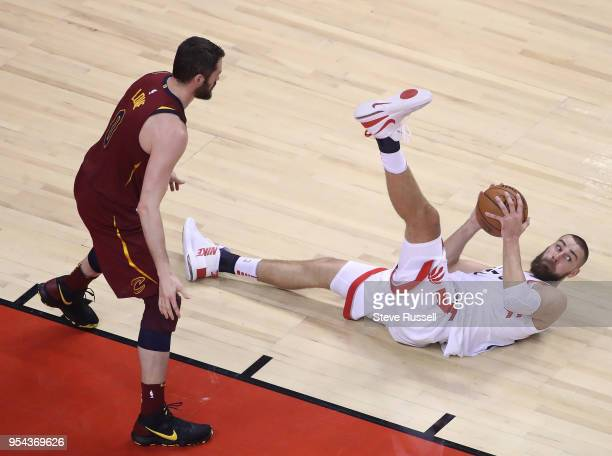 TORONTO ON MAY 3 Toronto Raptors center Jonas Valanciunas looks to make a pass from the floor as Cleveland Cavaliers center Kevin Love stands over...