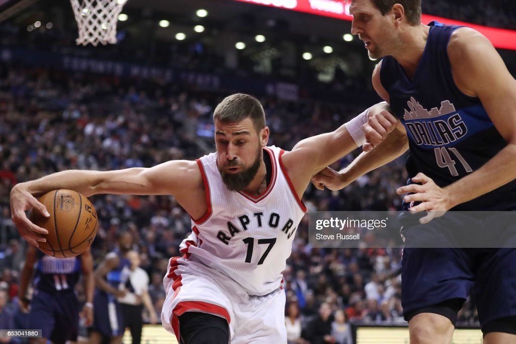 TORONTO, ON- MARCH 13 - Toronto Raptors center Jonas Valanciunas (17) scoops up a loose ball in front of Dallas Mavericks forward Dirk Nowitzki (41) as the Toronto Raptors play the Dallas Mavericks at the Air Canada Centre in Toronto. March 13, 2017.