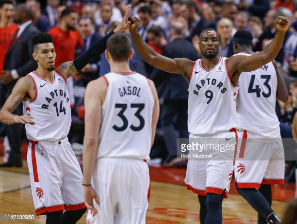 Toronto Raptors center Serge Ibaka and Toronto Raptors guard Danny Green high five as they come towards Toronto Raptors center Marc Gasol as the...