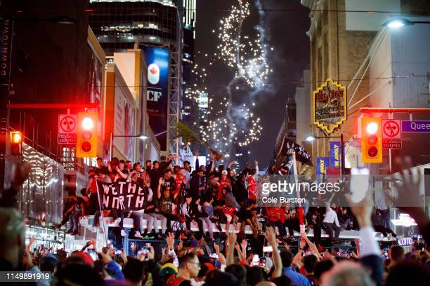 Toronto Raptors fans celebrate atop a bus after the team beat the Golden State Warriors in Game Six of the NBA Finals on June 13 2019 in Toronto...