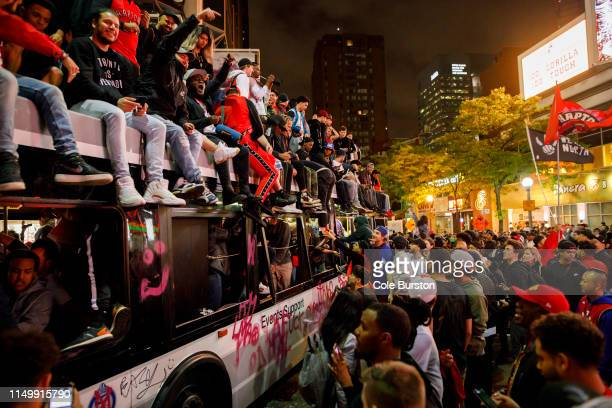 Toronto Raptors fans celebrate atop and inside a bus on Yonge St after the team beat the Golden State Warriors in Game Six of the NBA Finals on June...