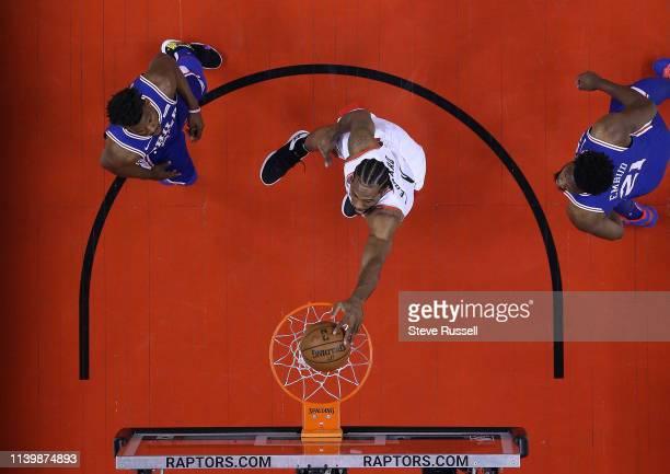TORONTO ON APRIL 27 Toronto Raptors forward Kawhi Leonard dunks as Philadelphia 76ers guard Jimmy Butler and Philadelphia 76ers center Joel Embiid...