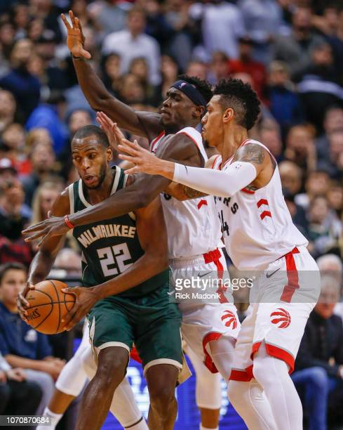 Toronto Raptors forward Pascal Siakam and Toronto Raptors guard Danny Green do their best to trap Milwaukee Bucks forward Khris Middleton who manages...