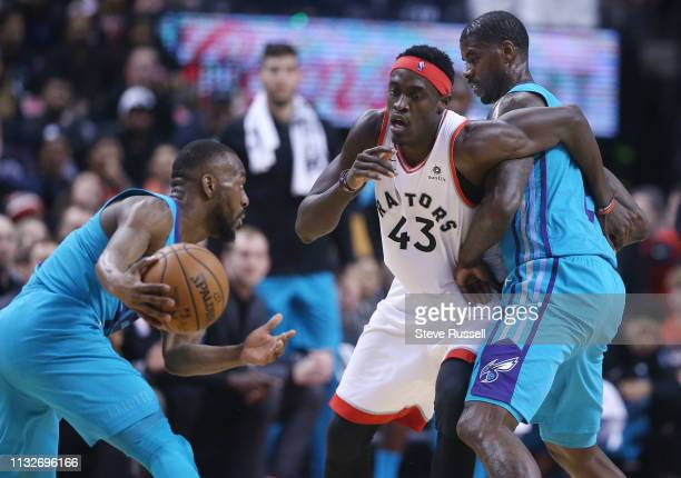 TORONTO ON MARCH 24 Toronto Raptors forward Pascal Siakam fights through a pick by Charlotte Hornets forward Marvin Williams trying to get to...