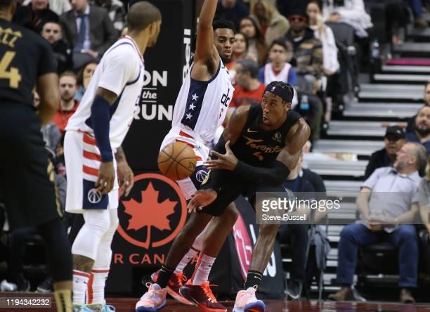 TORONTO ON JANUARY 17 Toronto Raptors forward Rondae HollisJefferson dishes off the ball past Washington Wizards guard Troy Brown Jr as the Toronto...