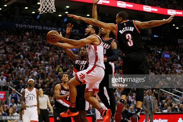 Toronto Raptors guard Cory Joseph goes to the basket while being guarded by Portland Trail Blazers center Ed Davis guard Damian Lillard and guard CJ...