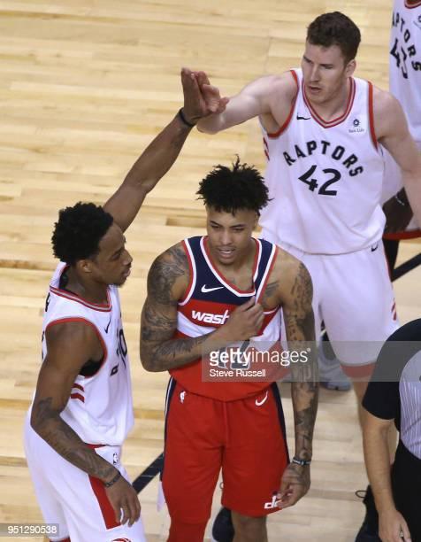 Toronto Raptors guard DeMar DeRozan and Toronto Raptors center Jakob Poeltl high five over Washington Wizards forward Kelly Oubre Jr. As the Toronto...