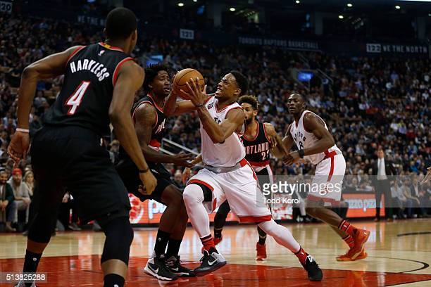 Toronto Raptors guard DeMar DeRozan drives to the basket past Portland Trail Blazers forward Maurice Harkless and Portland Trail Blazers centre Ed...