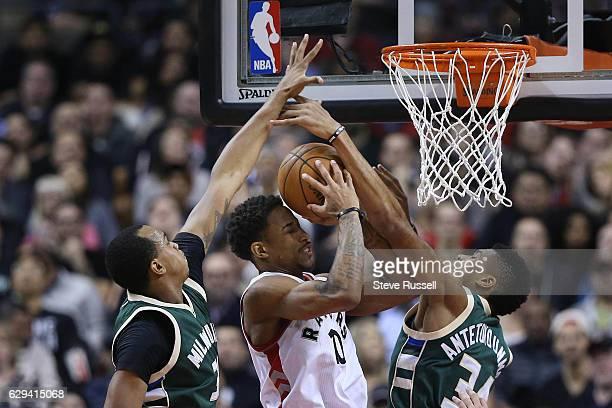 Toronto Raptors guard DeMar DeRozan is defended by John Henson and Giannis Antetokounmpo as the Toronto Raptors beat the Milwaukee Bucks 122-100 at...