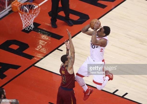 TORONTO ON MAY 3 Toronto Raptors guard DeMar DeRozan puts a shot over Cleveland Cavaliers guard George Hill as the Toronto Raptors play the Cleveland...