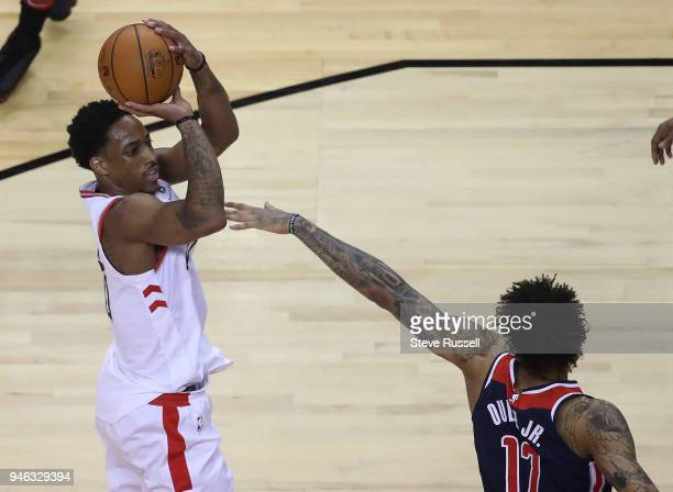 Toronto Raptors guard DeMar DeRozan puts up a shot over Washington Wizards forward Kelly Oubre Jr. As the Toronto Raptors open the first round of the...