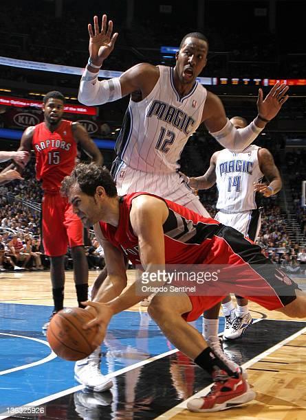 Toronto Raptors guard Jose Calderon hits the floor driving past Orlando Magic center Dwight Howard during the Raptors' 10296 loss to the Magic at...