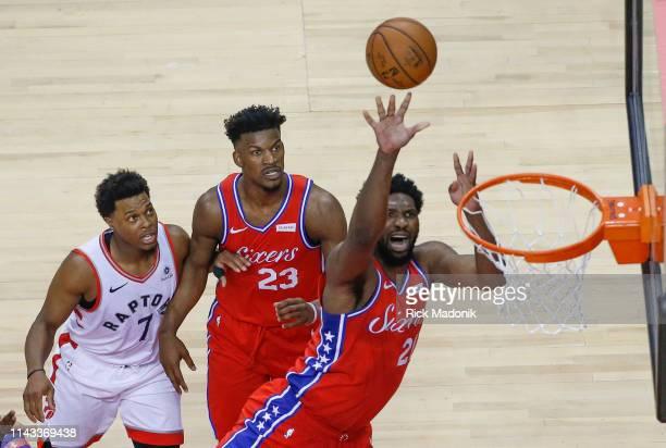 Toronto Raptors guard Kyle Lowry and Philadelphia 76ers guard Jimmy Butler have eyes as Philadelphia 76ers center Joel Embiid finishes Toronto...