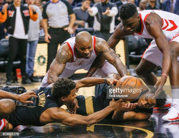 Toronto Raptors guard Kyle Lowry and Toronto Raptors guard DeMar DeRozan dive for a loose ball as Houston Rockets forward PJ Tucker starts his lunge...