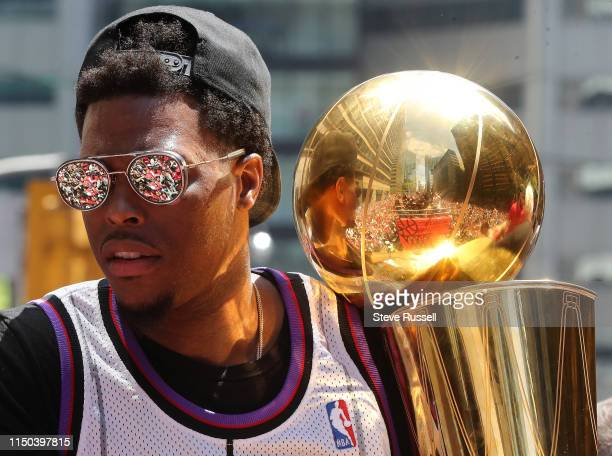 TORONTO ON JUNE 17 Toronto Raptors guard Kyle Lowry looks at the fans while holding the trophy as the Toronto Raptors hold their victory parade after...