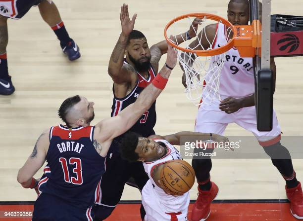 Toronto Raptors guard Kyle Lowry sneaks under Marcin Gortat and Markieff Morris as the Toronto Raptors open the first round of the NBA playoffs...