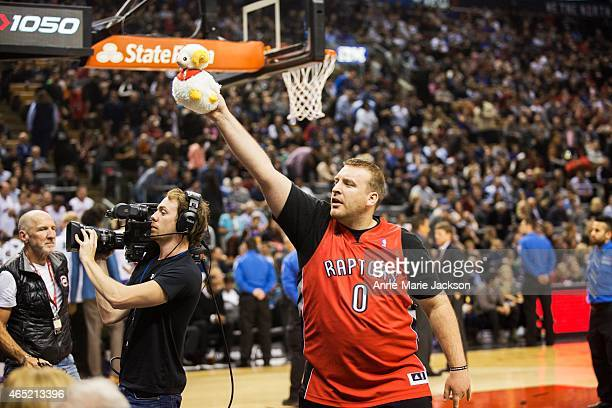 Toronto Raptors Interactive Squad member Trevor Stone gives out a toy goat to fans celebrating Chinese New Year during a game against the Golden...
