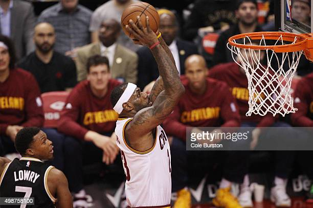 TORONTO ON NOVEMBER 25 Toronto Raptors' Kyle Lowry watches as Cleveland Cavaliers' LeBron James heads to the net for a dunk during NBA basketball...