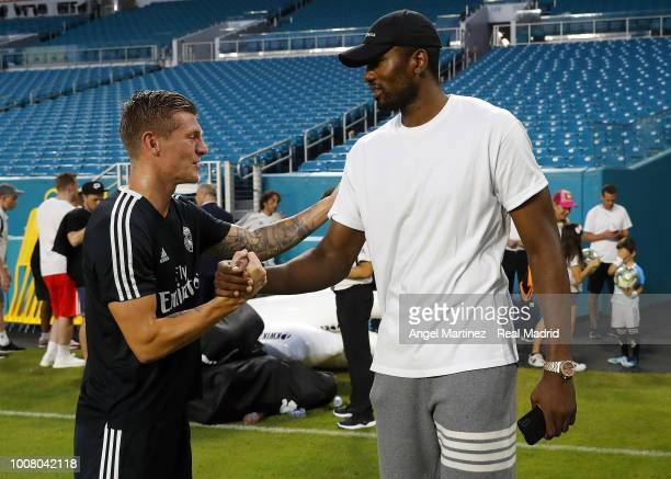 Toronto Raptors NBA player Serge Ibaka shakes hands with Toni Kroos of Real Madrid after a training session at Hard Rock Stadium on July 30 2018 in...