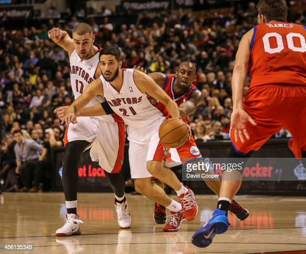 Toronto Raptors new point guard Greivis Vasquez drives in the paint around Philadelphia 76ers center Spencer Hawes late in the game as theToronto...